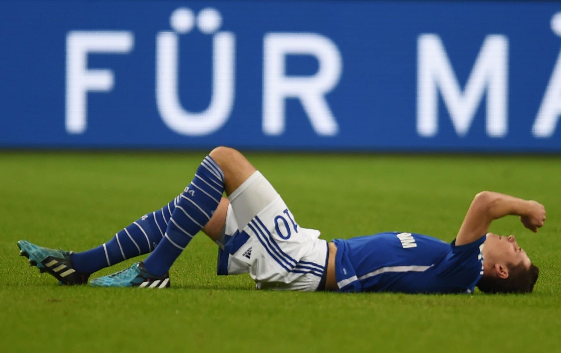 Schalke's midfielder Julian Draxler lays injured on the pitch and had to be taken off during the German First division Bundesliga football match FC Schalke 04 vs FC Augsburg in Gelsenkirchen, western Germany. AFP PHOTO / PATRIK STOLLARZ RESTRICTIONS / EMBARGO DFL RULES TO LIMIT THE ONLINE USAGE DURING MATCH TIME TO 15 PICTURES PER MATCH. IMAGE SEQUENCES TO SIMULATE VIDEO IS NOT ALLOWED AT ANY TIME. FOR FURTHER QUERIES PLEASE CONTACT DFL DIRECTLY AT + 49 69 650050. (Photo credit should read PATRIK STOLLARZ/AFP/Getty Images)